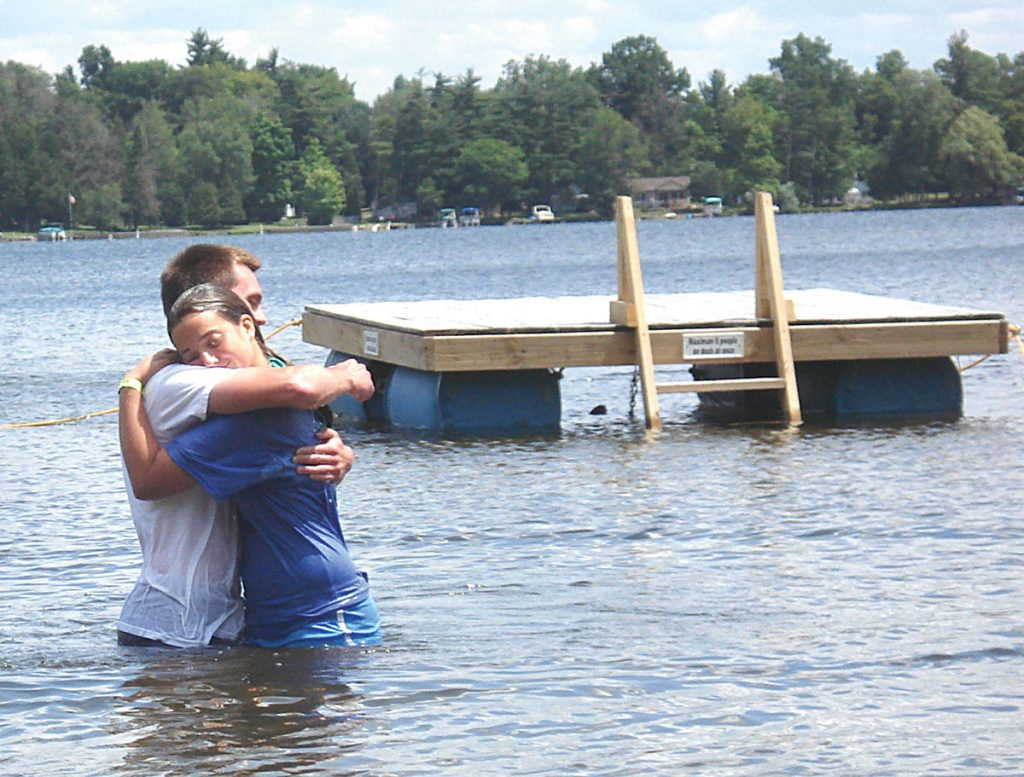 Brandon Armstrong hugs his cousin Rachel Weldy after baptizing her at Michigan Christian Youth Camp in Attica. Rising costs and increased competition challenge Bible camps nationwide