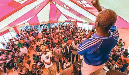 Evangelist Aubrey Malire preaches under a tent in Kwanzama
