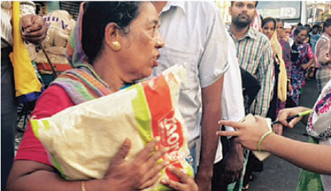 A flood victim receives a bag of rice from church members in Chennai