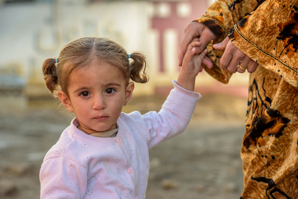 A 15-month-old Syrian refugee girl holds her mother's hand at a tented settlement in Lebanon.