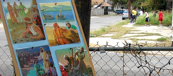 In 2008, in the Hollygrove area of New Orleans, a Bible storyboard is leaned against a tree. Across the street, minister Charles Marsalis and his young friends search for a football lost in the weeds.
