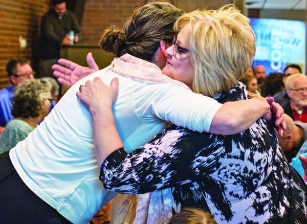 Deb Smeltzer, right, hugs a fellow Christian on the new congregation's first day of worship at the Red Bridge Road location.