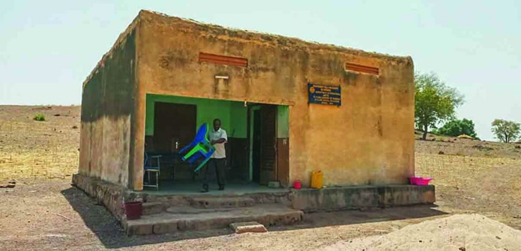 Muhindo Malembe sets up chairs outside the humble building that serves as a maternity ward for the village of Difemou in the West African nation of Mali.
