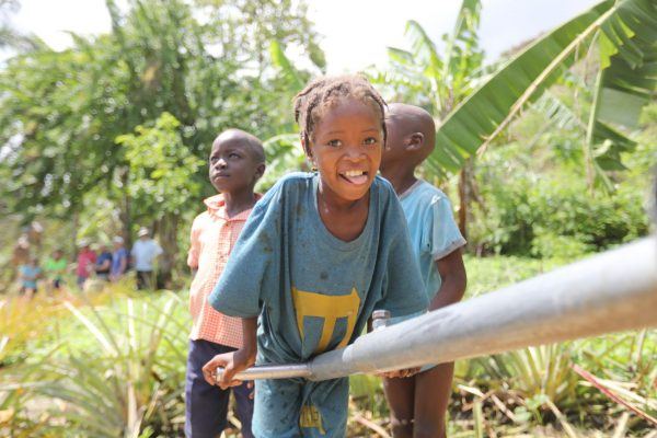 A Haitian girl pumps a water well drilled by Healing Hands International.
