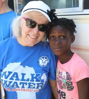 Janice Fuller, coordinator of the Walk4Water fundraiser at the Brentwood Oaks Church of Christ in Austin, Texas, poses with a Haitian girl at the site of Healing Hands' 1,000th well.