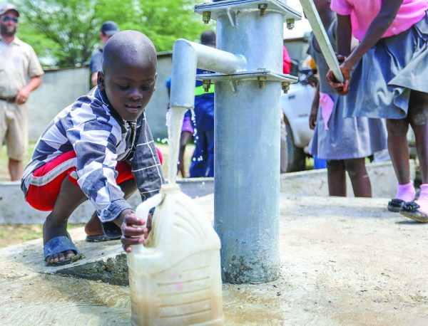 A boy in La Tremblay, Haiti, fills a jug with water at the site of Healing Hands International's 1,000th well.