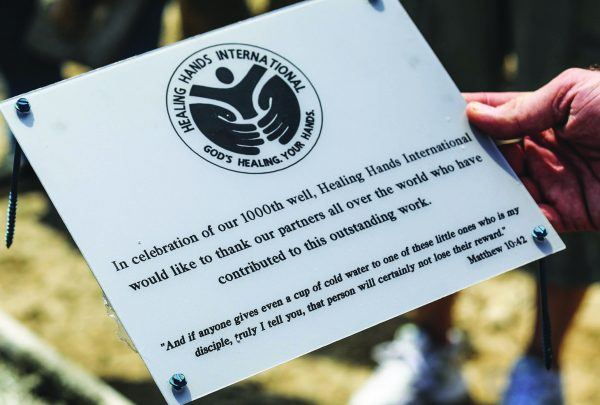 A plaque marks the site of Healing Hands International's 1,000th well.
