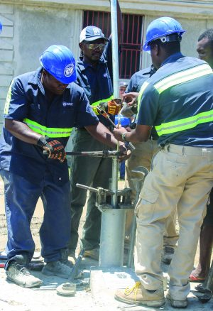 Haitian employees of Healing Hands International work on the 1,000th well.