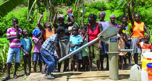 Women and children show their enthusiasm over the well drilled by Healing Hands International in the village of Akdesé, Haiti.