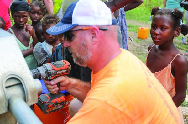 Jason Carroll places a plaque in memory of the late Ronald Kay White, a longtime Healing Hands supporter, on a well pump in the mountain village of Akdesé, Haiti.