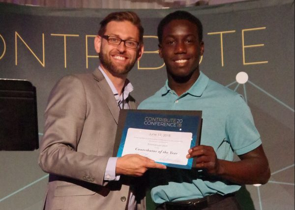 Emmanuel Ukot accepts an award from Brandon Tatum at the Contribute conference.