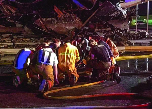 Volunteer firefighters take time to pray after battling the church fire in Kermit, Texas.