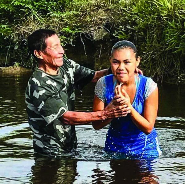 Monkey Mountain minister Paul Daniels baptizes one of four youths immersed during a mission trip by the Amelia's Ward team.