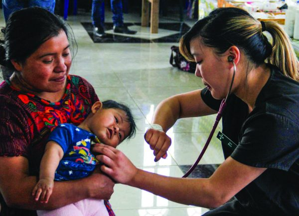 Jan Bian, who just graduated from Oklahoma Christian University with a degree in biology and plans to attend medical school, measures the heart rate of a Guatemalan infant. She and fellow students took vitals and assisted physicians.