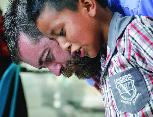 Eric Phelps, trip coordinator and former chair of biology at Oklahoma Christian, helps a young Guatemalan reads his weight.