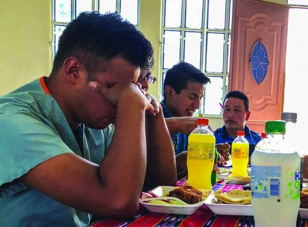 Health Talents' Guatemalan workers pray before eating lunch during the Mactzul Quinto clinic. The ministry conducts clinics in the buildings of Churches of Christ, and church members provide the visiting medical workers with meals.