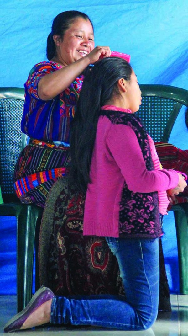 A Mayan mother helps her daughter in the Health Talents sponsorship program get ready for a photo.