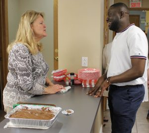 Bev Pearman visits with a Ville-Émard church member at the fellowship meal.