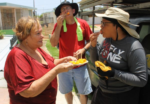 Annea Soto offers papaya grown in her back yard to Terrell Lee and Charidy Dobbins.