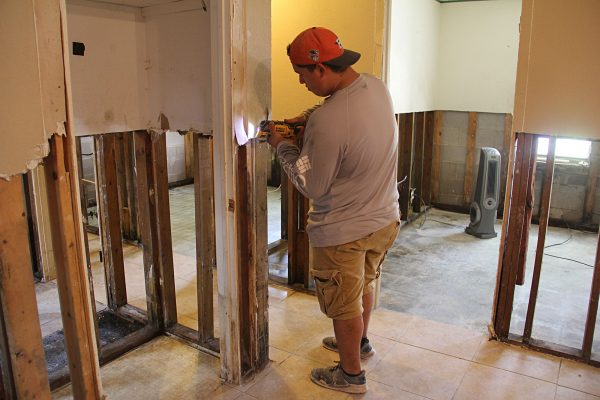 A church volunteer strips drywall from a flood-damaged home in Weslaco, Texas.