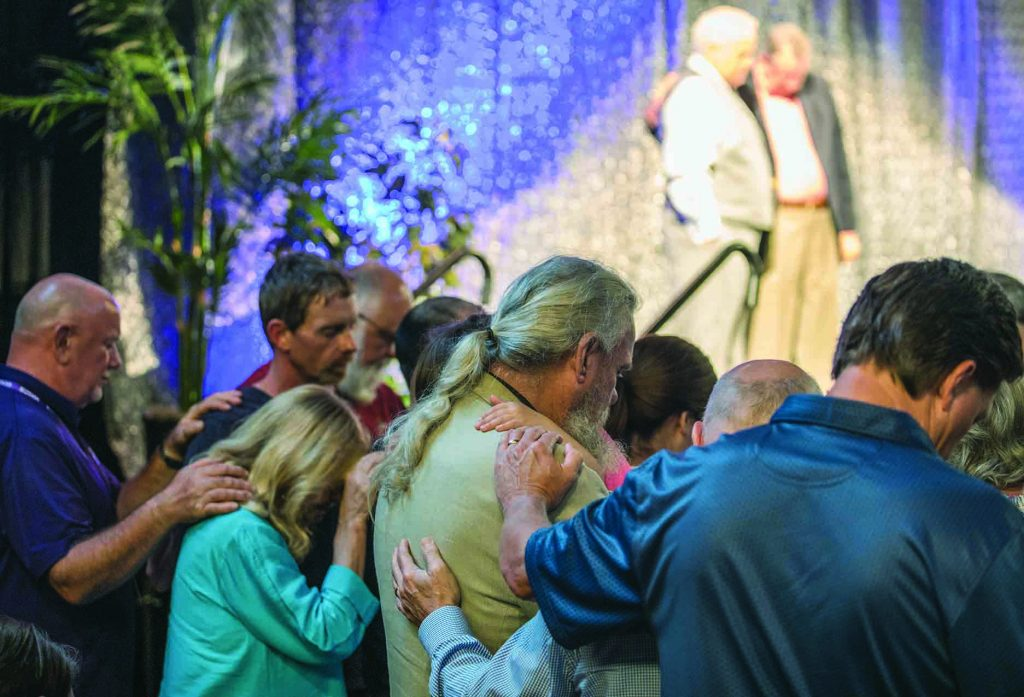 Ministers, elders and their wives from congregations across the nation surround members of the Burnetter Chapel Church of Christ as Lipscomb University's President Randy Lowry prays with the church's minister, Joey Spann, on stage during Lipscomb's Summer Celebration.