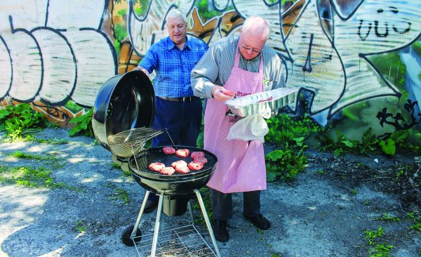 Ron Pearman, right, and Doyle Martin grill burgers at the Ville-Émard church.