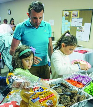 Horald Shabanaj and daughters Isabelle, 8, and Vanessa,10, fill their plates at a church fellowship meal.