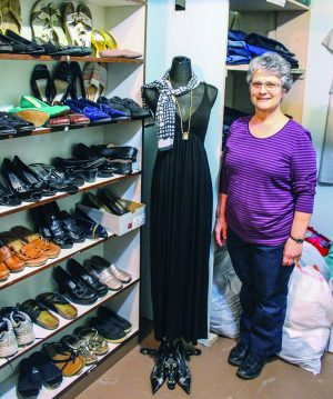 Eva King, wife of elder Gary King, poses in the congregation's clothing closet, which covers much of the basement.