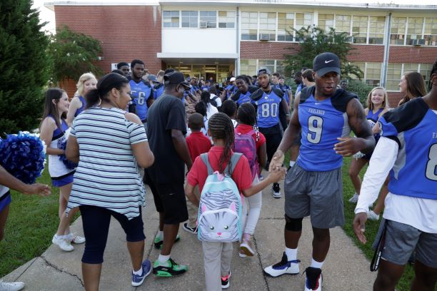 Faulkner University football players and cheerleaders greet Davis Elementary students back to school on Monday with claps and high-fives outside the school.