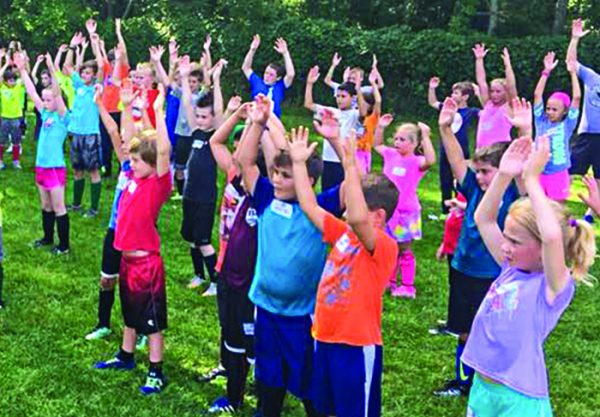 Young soccer players raise their arms during a drill at the church's soccer camp.