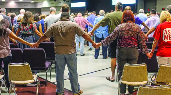 Members of The Park Church of Christ in Tulsa, Okla., hold hands as they pray at the end of their first service at their new location.