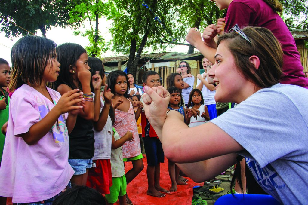 Students from Southwest Christian School in Fort Worth, Texas, sing songs with children in Talisay City on the island of Cebu in the Philippines during a mission trip.