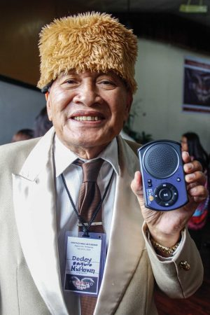 Longtime church leader Dodoy Sameon shows off his new solar player.