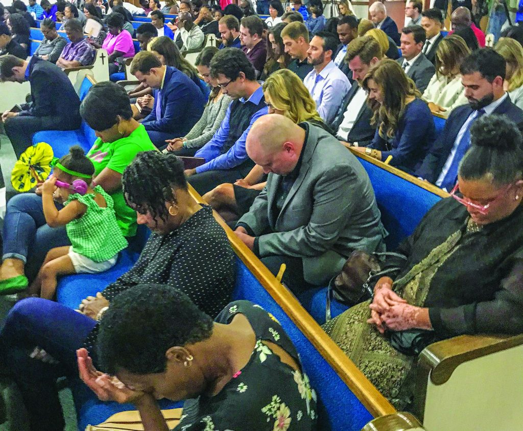 Loved ones, including friends, relatives and fellow Christians, pray Saturday night at a prayer vigil in Botham Shem Jean's memory. The Dallas West Church of Christ hosted the vigil.