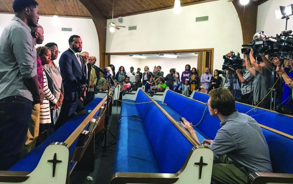 Attorney Lee Merritt, with Allison Jean to his right, speaks to the news media at the Dallas West Church of Christ on Saturday.