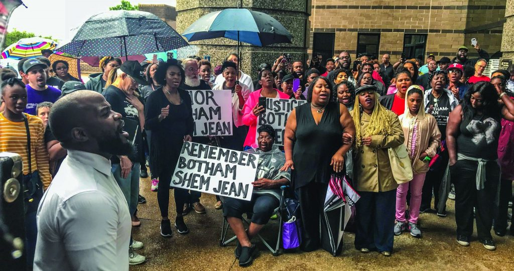 Willie Williams III, left, minister for the North Colony Church of Christ, north of Dallas, sings at a #Justice4Botham event outside the Dallas County courts building. Williams, a former Abilene Christian University football player, organized the social media campaign.