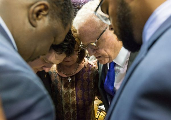 Praying at the center's opening are, from left, Jerry Taylor, Gavin Rogers, Claudette Rogers, Royce Money and Tryce Prince.