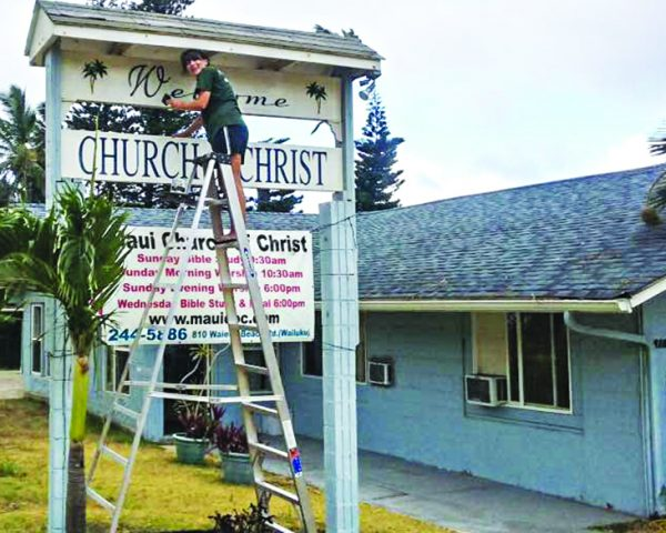 Macy Elander cleans and puts protective enamel on the sign at the Maui Church of Christ in Wailuku, Hawaii.
