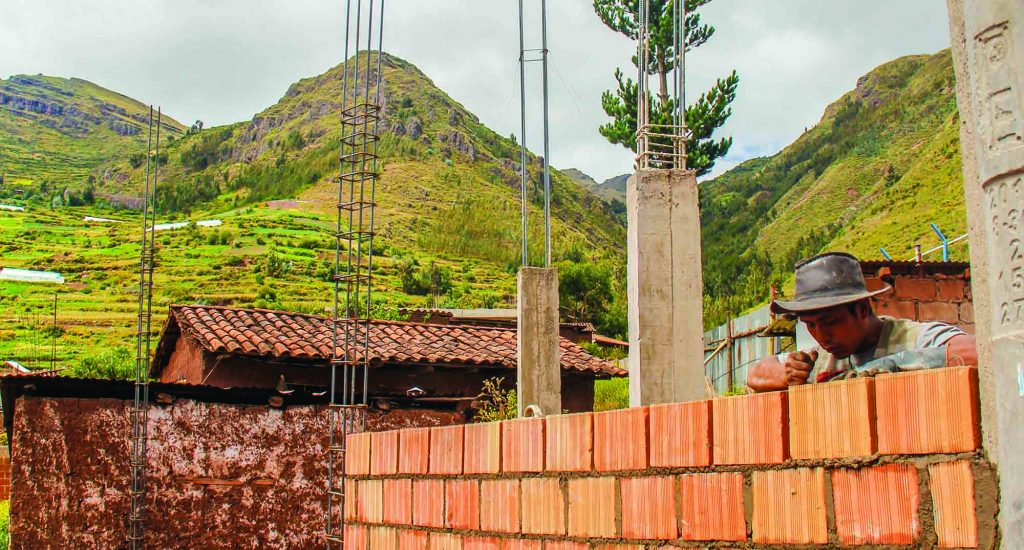 In the mountains near Cuzco, Peru, a worker lays bricks for a new, multi-story meeting place of the Huancalle Church of Christ. Church members contributed funds for the construction.
