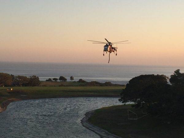 A helicopter stops at Pepperdine University's reclaimed water pond to pick up water in the fight against the Woosley Fire.
