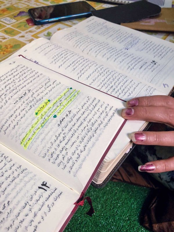 On top of a Farsi-language Bible open to the prophet Isaiah, Miriam flips through her own copy of a Farsi New Testament. She has highlighted the parable of the Pearl of Great Price in the Gospel of Matthew.