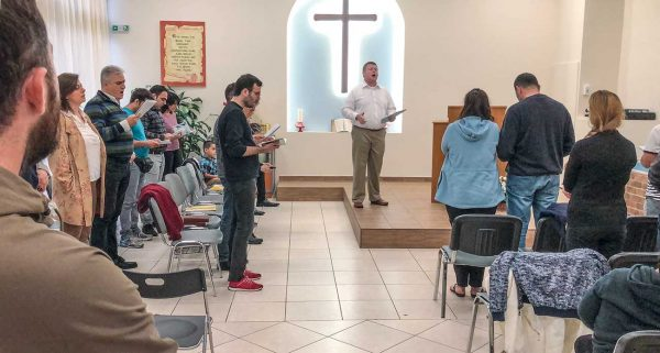 Ibrahim, far right, and fellow Persian believers sing during a Sunday night worship service with the Glyfada Church of Christ before three Iranians are baptized.