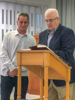 Alexander Melirrytos, right, and a translator deliver a sermon to the Omonia church.