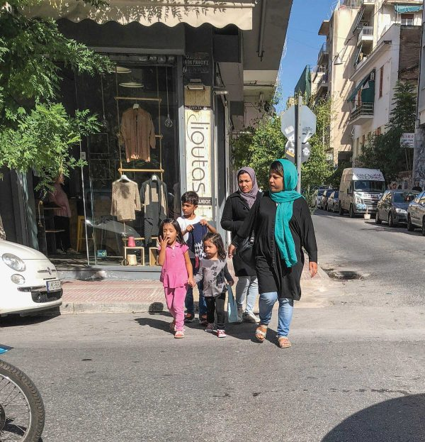 Muslim women and children cross a street in the Athens neighborhood of Omonia.