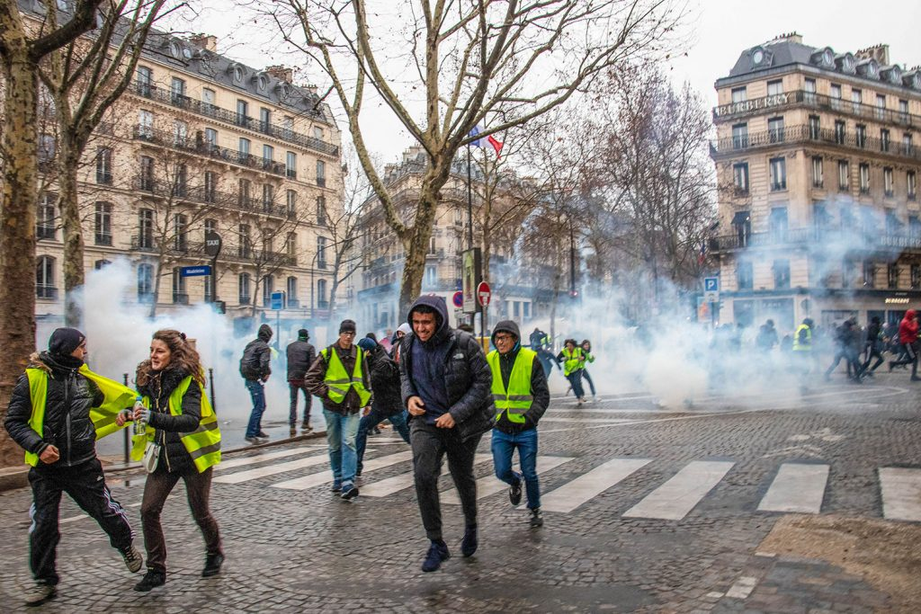 Yellow vest protesters run from tear gas in Paris.