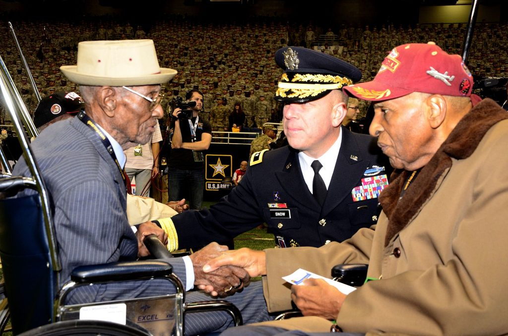 Richard Overton (left), America's oldest veteran at 109 years old, greets Dr. Granville Coggs (right), a Tuskegee Airmen, and Maj. Gen. Jeffery Snow (center), commanding general of U.S. Army Recruiting Command, during the pre-game ceremonies of the 2016 U.S. Army All-American Bowl, Jan. 9. Overton delivered the game ball for the bowl, while Coggs was introduced to crowd with fellow Tuskegee Airmen Theodore Johnson during opening ceremonies.