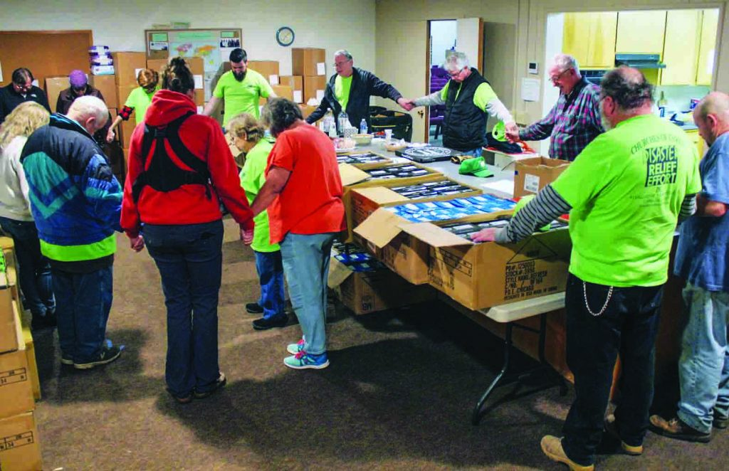 In the meeting place of the Chico Church of Christ in California, volunteers pray before distributing relief supplies to victims of the Camp Fire.