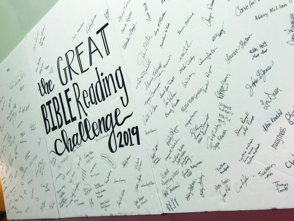 A banner shows the names of church members who have signed up for the Bible reading challenge.