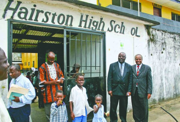 The Wells-Hairston High School in the West African nation of Liberia was co-founded by R.C. Wells and Andrew Hairston. Jack Evans (right, red tie) visited the campus in 2005. Evans, a longtime friend of Wells, is president emeritus of Wells alma mater, Southwestern Christian College in Texas. Next to Evans is Liberian minister Ofusu Bomeo. At left is Liberian evangelist and Southwestern alum Arthur David.
