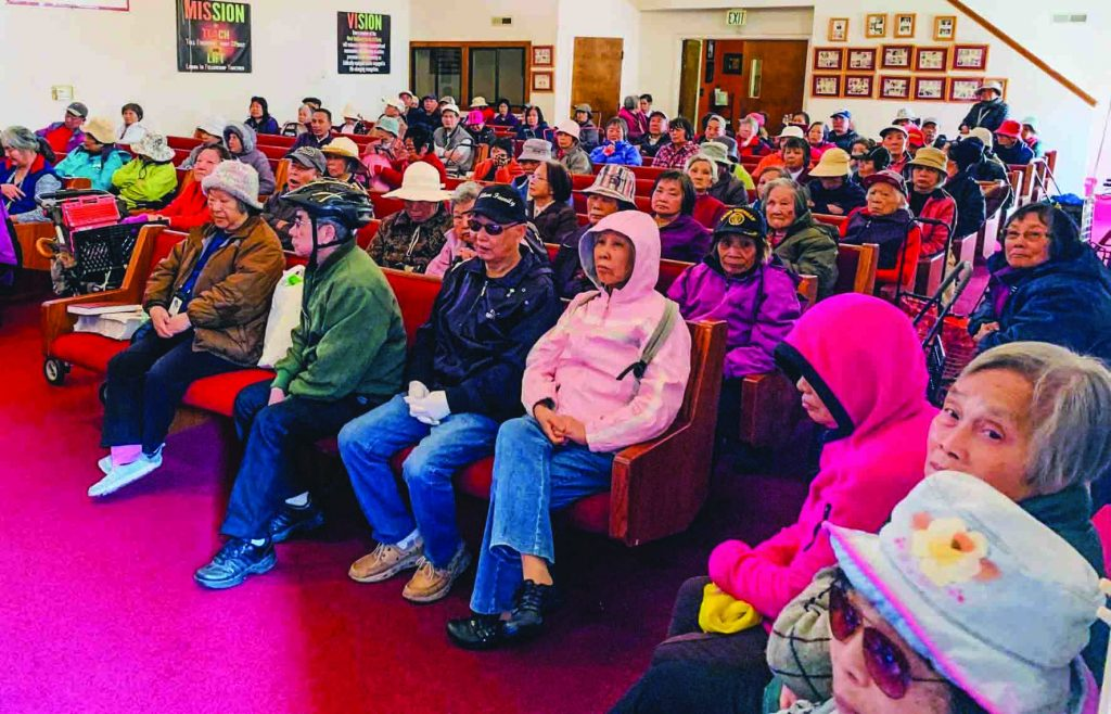 People from the San Francisco Bay area gather in the meeting place of the West Oakland Church of Christ during the church's monthly outreach and food giveaway.